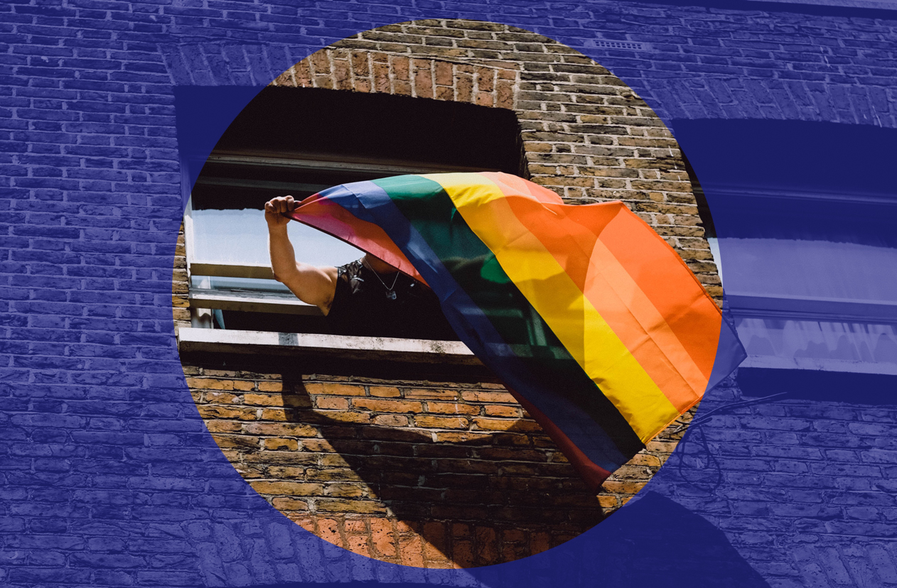 Rainbow flag being hung out of a window